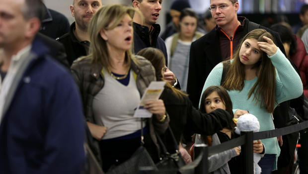 Travelers wait in line to board a flight at LaGuardia Airport in New York Nov. 26, 2013.