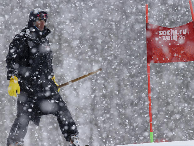 A ski course worker waits with a shovel under heavy snow fall just before the start of the second run of the women's giant slalom at the Sochi 2014 Winter Olympics, in Krasnaya Polyana