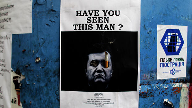 A poster with a photo of fugitive Ukrainian President Viktor Yanukovich, who fled the capital Kiev and went into hiding after months of protests against his government, is seen fixed onto a barricade in central Kiev