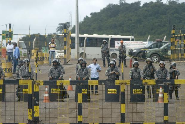 Police officers stand guard during a demonstration against Norte Energia - the company responsible for the construction of Belo Monte hydroelectric power plant - demanding compensation for the loss of income from the flooding of the Xingu river near Altamira, in the northern state of Para, Brazil