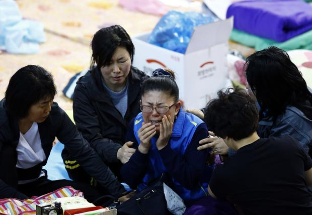 A family member of a missing passenger of capsized passenger ship Sewol which sank last Wednesday, cries after she identified her family member on a list of newly found bodies on a noticeboard at makeshift accommodation at a gymnasium in the port city of Jindo