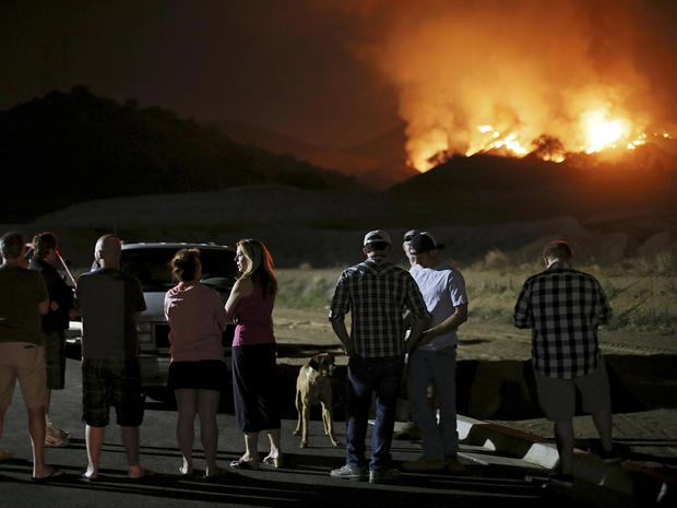 Residents watch a fast-moving wildfire approach in San Marcos, California, May 14, 2014.