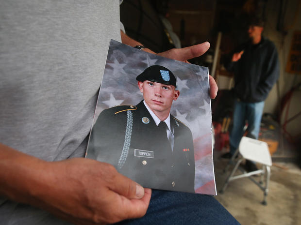 Jack Winter holds a picture of his nephew Aaron Toppen as family and friends gather to grieve at Toppen's mother's home