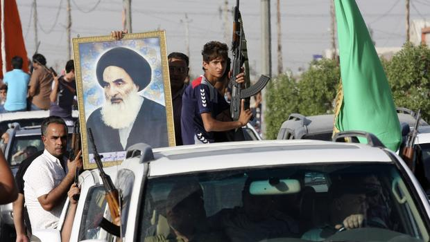 Volunteers who have joined the Iraqi Army to fight against predominantly Sunni militants carry weapons and a portrait of Grand Ayatollah Ali al-Sistani during a parade in Baghdad's Sadr City