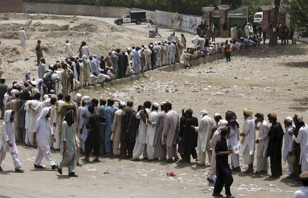 People who fled the military offensive against Pakistani militants in North Waziristan line up to receive food from the army in Bannu, in Pakistan's Khyber Pakhtunkhwa province