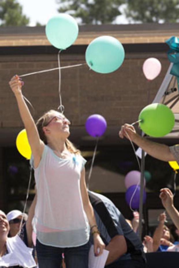 Cassidy Stay是她父母和兄弟姐妹大规模射击的唯一幸存者,他们在2014年7月12日在德克萨斯州春天举行的Lemm小学庆祝Stay家庭生活的社区纪念活动中放了一个气球。