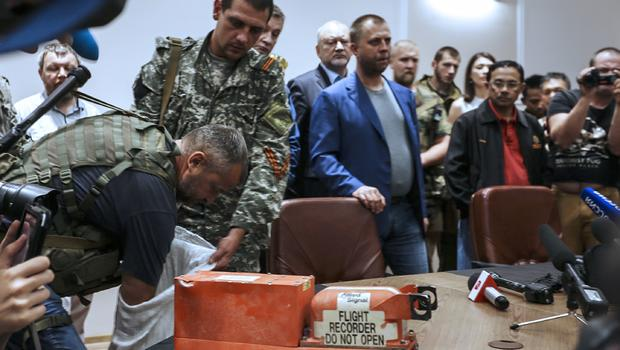 "A pro-Russia separatist shows members of the media a ""black box"" from Malaysia Airlines flight 17, before handing it over to Malaysian representatives during a press conference in Donetsk"