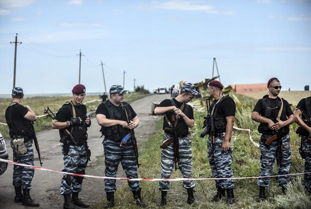 Armed pro-Russian separatists stand guard in front of the crash site of Malaysia Airlines Flight 17 near the village of Grabovo