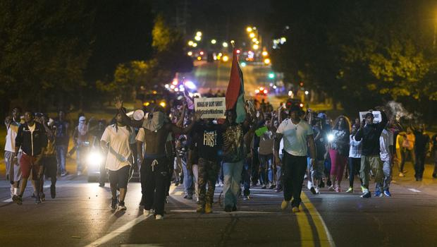 Demonstrators march in street while protesting the shooting death of Michael Brown in Ferguson, Missouri on August 12, 2014
