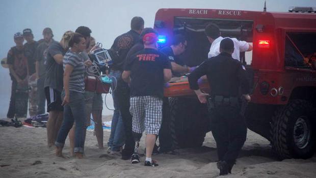 2014年8月29日,在俄勒冈州林肯市,一名9岁的女孩被困在沙滩下,当一个沙洞倒塌时被送入救护车。