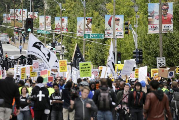 2014年10月11日,在圣路易斯举行的抗议枪支暴力和佛罗里达州弗格森,少年迈克尔·布朗拍摄的抗议活动期间,庆祝圣路易斯红雀队季后赛棒球成功线路市场街的旗帜作为示威者游行。