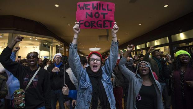2014年11月28日,在密苏里州圣路易斯广场购物中心游行时,抗议者要求杀害18岁的迈克尔·布朗,要求正义。