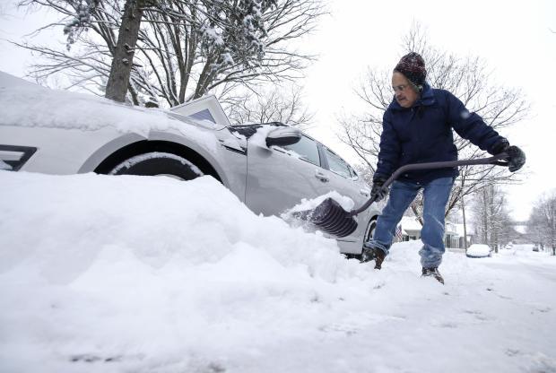 Mike Mindel于2015年1月6日在印第安纳州Zionsville的汽车周围清除积雪。