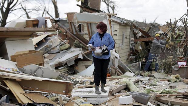 一名妇女在2015年4月10日在伊利诺伊州罗谢尔被龙卷风摧毁的房屋的残骸中搜寻后,拿着她的财物。