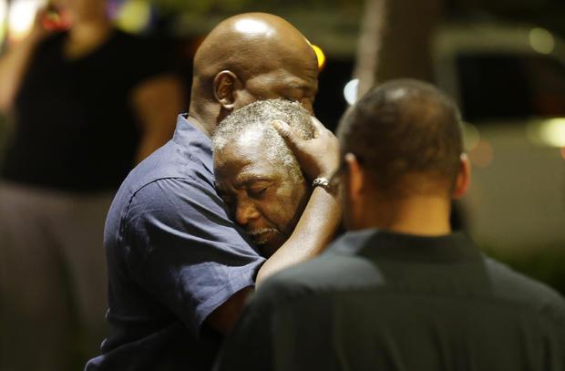 在2015年6月17日晚上,在查尔斯顿,S.C.,崇拜者在2015年6月17日晚上从历史悠久的黑人教堂射击场景中穿过街道群体祈祷。