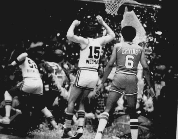 这张1979年11月的档案照片显示堪萨斯城国王的斯科特韦德曼和费城76人队的朱利叶斯欧文看着国王队的比尔罗宾兹,左,76人队的达里尔道金斯在篮球比赛中击败玻璃篮板后跑来跑去掩护