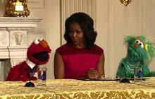Michelle Obama and Elmo compare muscles