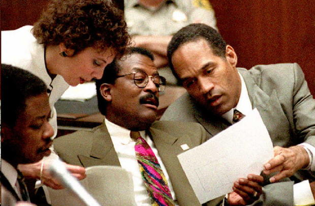 Murder defendant O.J. Simpson, prosecutor Marcia Clark and defense attorney Johnnie Cochran Jr., center, look over documents during the afternoon session of the O.J. Simpson double murder trial in Los Angeles, California, on Feb. 21, 1995. Defense attorne