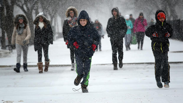 Schoolchildren run along the National Mall as snow begins to fall Jan. 22, 2016, in Washington, D.C.