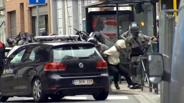 Armed Belgian police apprehend a suspect in this still image taken from video in the Molenbeek neighborhood of Brussels, Belgium, March 18, 2016.