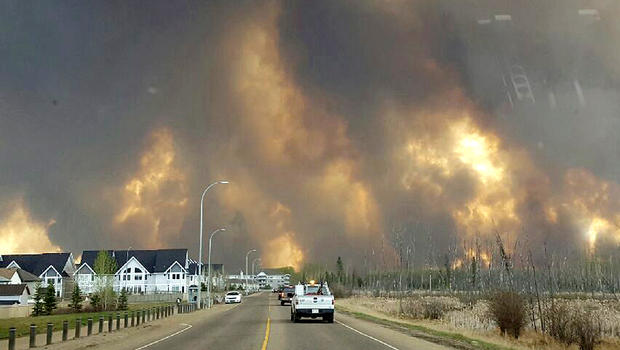 This photo taken through a car windshield shows smoke rising from a wildfire raging outside of Fort McMurray, Alberta, May 3, 2016.