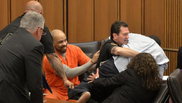 一名法庭官员解决了俄亥俄州连环杀手迈克尔·麦迪逊的三名受害者之一的父亲,他离开后,在法官宣布在凯霍加县普通法院判处死刑的几分钟后,他跳过一张桌子在法庭上攻击被告。