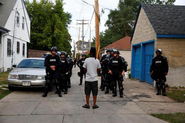 2016年8月15日威斯康星州密尔沃基警方开枪射击一名男子后,警察穿着防暴装置在巷子里集结。