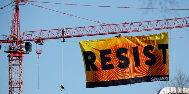 """绿色和平组织的积极分子举行反特朗普抗议活动,因为他们在2017年1月25日在华盛顿白宫附近的一座建筑起重机上展示了""""抵抗""""的横幅。"""