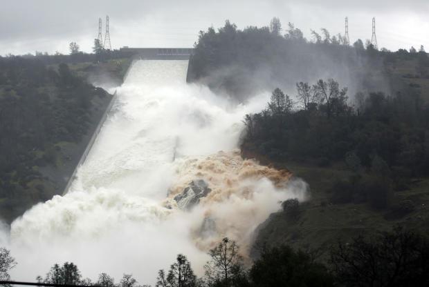 2017年2月9日,在Oroville,加利福尼亚州的Oroville大坝溢洪道的墙壁上,水流经过。
