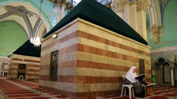 A Palestinian woman reads the Quran inside Ibrahimi Mosque, which Jews call the Tomb of the Patriarchs, in the West Bank city of Hebron July 7, 2017.