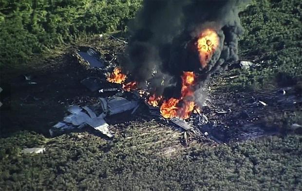 2017年7月10日,在伊利诺伊州伊塔贝纳的一个农田中坠毁的军用飞机上冒烟和火焰。