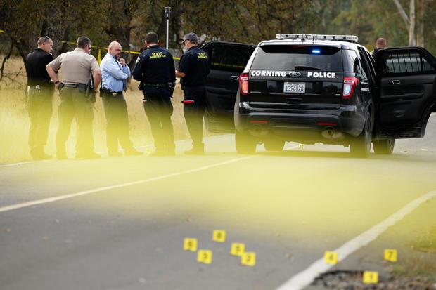 执法人员和调查员在2017年11月14日在加利福尼亚州Rancho Tehama参与射击的警车附近交谈。