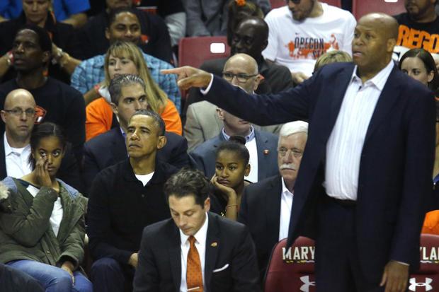 奥巴马和女儿们在马里兰州大学公园举行的NCAA男子篮球比赛中观看总统的姐夫克雷格罗宾逊