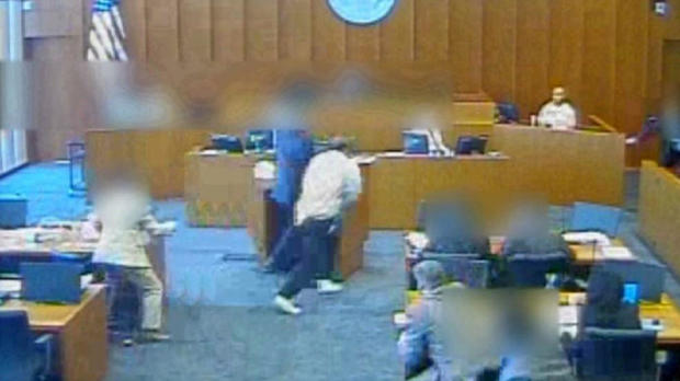 In this image capture from video provided to CBS Salt Lake City affiliate KUTV, Siale Angilau, center, rushes the witness stand in a federal courtroom in 2014.