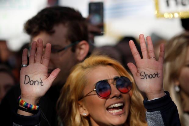"""一名示威者高呼学生和枪支管制倡导者在华盛顿举行的一次集会上最近的学校枪击事件后举行""""为我们的生命进行的三月""""活动,要求控制枪支"""