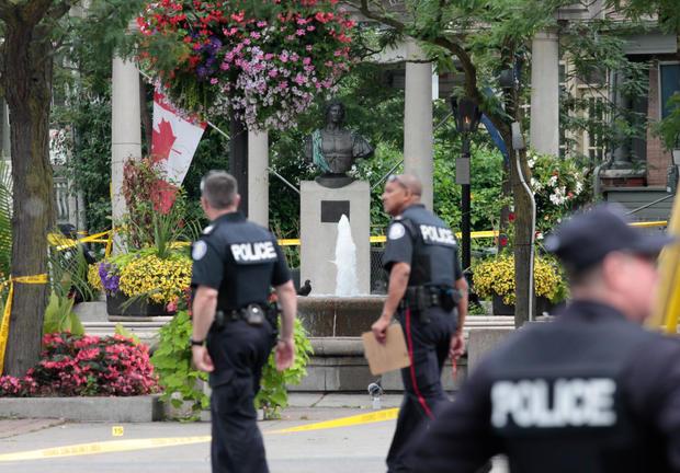 在多伦多大规模枪击事件发生后,警察走过亚历山大大公园