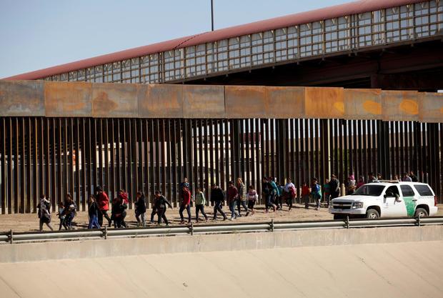美国海关和边境保护局(CBP)官员在美国德克萨斯州埃尔帕索非法进入美国请求庇护后,护送人员在华雷斯城拍摄的这张照片中