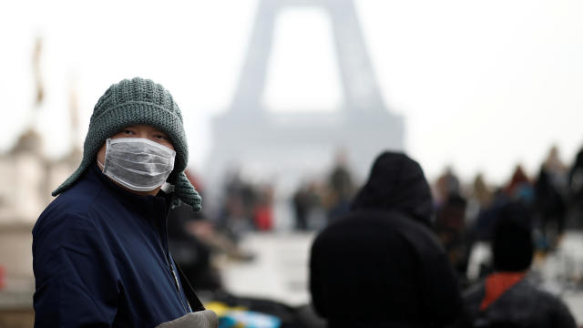 A man wears a face mask on the Trocadero esplanade in front of the Eiffel Tower in Paris, France, January 25, 2020.