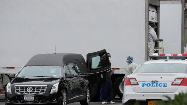 A hearse is parked next to refrigerated tractor trailers, that are being used as morgues for body transfer outside Icahn Stadium on Randall's Island in New York