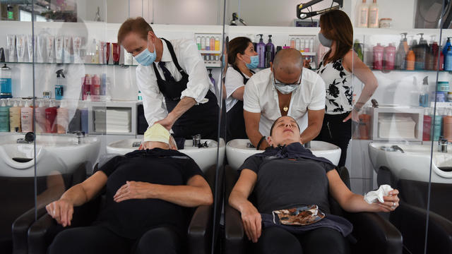 Women are separated by dividers as they have their hair washed after social distancing guidelines to curb the spread of the coronavirus disease (COVID-19) are relaxed, at Bella Rinova in Houston