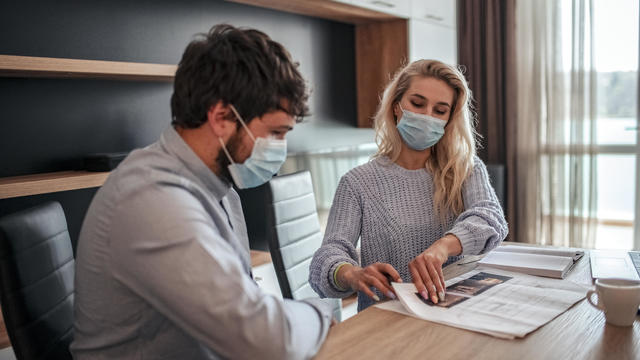 man and woman working with protective masks at home
