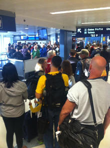 Travelers at Chicago O'Hare International Airport gather after a fire at a FAA facility led to a ground stop of all flights in and out of Chicago's airports.