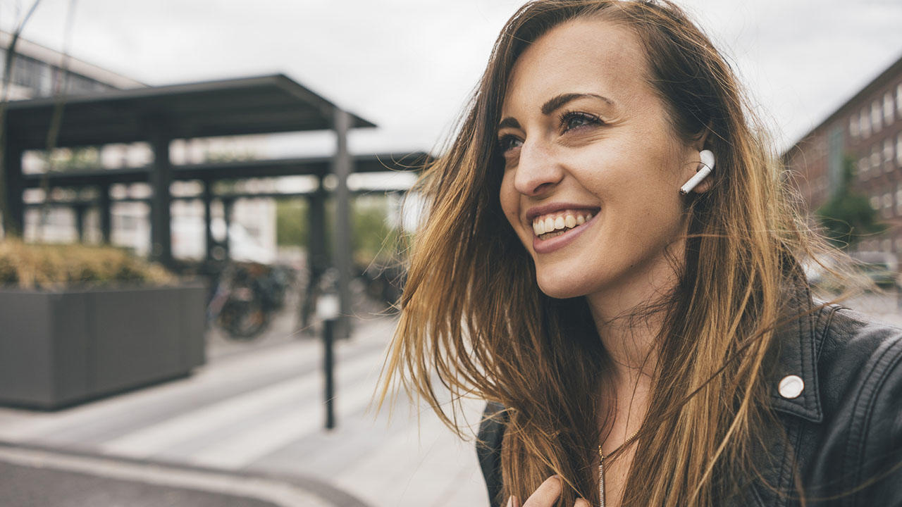 Smiling woman wearing wireless earbuds