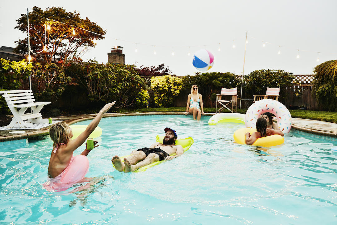Smiling friends playing in backyard pool during party on summer evening