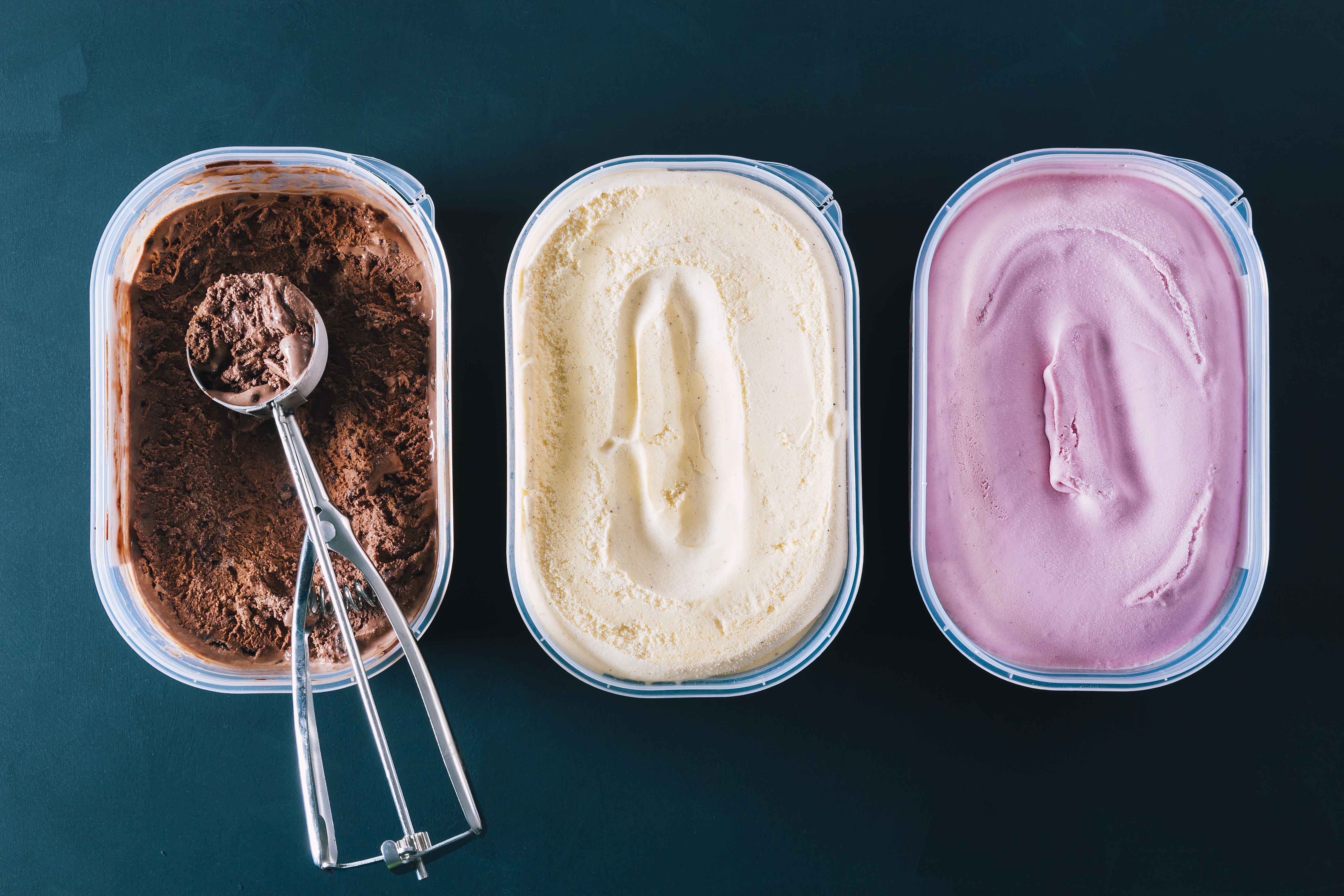 Chocolate, vanilla and strawberry ice cream tubs with scoop