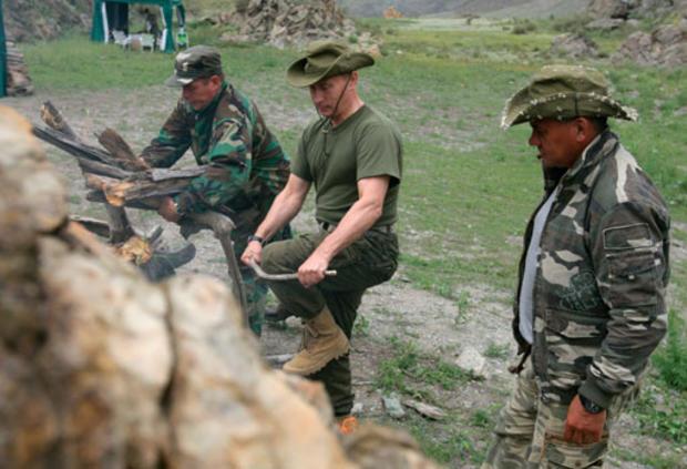 Vladimir Putin breaks a tree branch for a bonfire