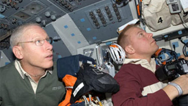 Mission specialists Patrick Forrester (left) and Tim Kopra work on the flight deck of space shuttle Discovery.