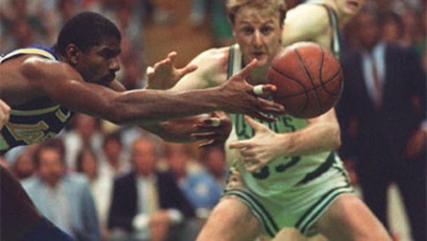 """Earvin """"Magic"""" Johnson of the Los Angeles Lakers reaches for a loose ball in front of Larry Bird of the Boston Celtics"""