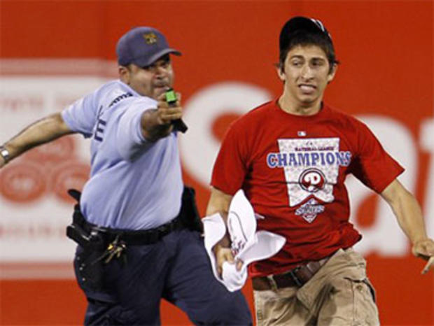 A law enforcement officer chases down a fan who ran onto the field before the eighth inning of a baseball game between the Philadelphia Phillies and the St. Louis Cardinals, Monday, May 3, 2010, in Philadelphia. St. Louis won 6-3. (AP Photo/Matt Slocum)