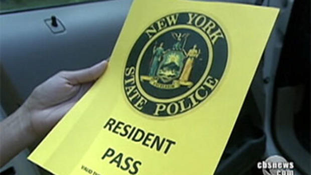 Rhinebeck, N.Y., resident Andrea Lavin holds a special pass she needs to get past security guards and access her house during Chelsea Clinton's wedding.